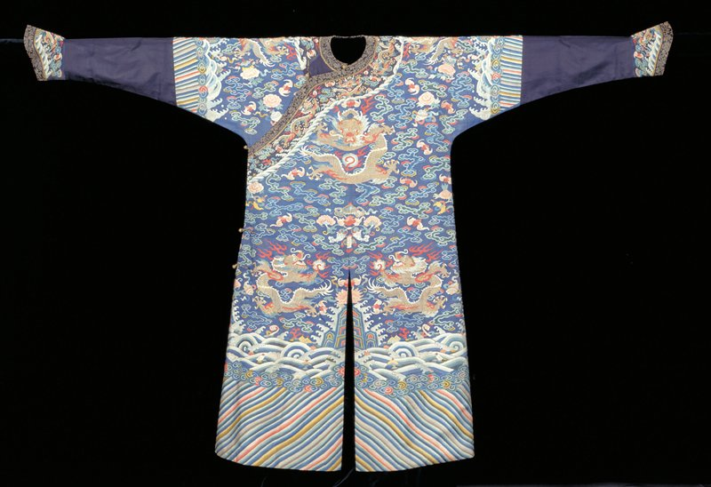 Court robe of dark blue k'ossu with nine 5-clawed dragons in gold, those in profile grasping Heavenly jewel. In ground loose cloud forms, bats, peonies, Buddhist symbols in shades of red, rose, blue, green, yellow, peach, dull mauve, and olive green. Conventional border of slightly wavy slanting stripes. Tight clouds below rolling waves in which appear Taoist symbols, a 'cash' and jui sceptre, coral. Below sleeve border a strip of midnight blue silk damask, medallion design. Cuffs and collar band of dark blue k'ossu edged with black and gold brocade. Slit back and front. Lining of blue satin damask. Much painted detail; k'ossu loose, especially in dragon area. Some mending.
