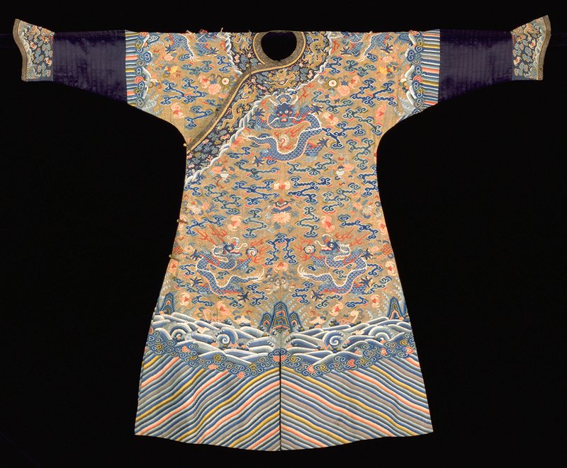 Imperial robe of k'ossu with gold thread background and nine 5-clawed dragons in blue, those in profile grasping the Heavenly Jewel. In the ground, loosely-drawn clouds, bats, peonies, and Buddhist symbols in tones of blue, red, rose, green, brown, black, mauve. Border of slanting, straight stripes, in body colors plus yellow, toped with spray and curling waves in which appear symbols of the Eight Precious Things. Same border design on sleeve above a strip of blister ribbed dark blue satin ending in blue k'ossu cuffs with bats and universe design. Same collar band, but with coral sprays in waves. Note painted areas in waves and dragon details. Robe slit front and back and lined with thn blue silk. The k'ossu in this robe coarse, and with many breaks on shoulders.