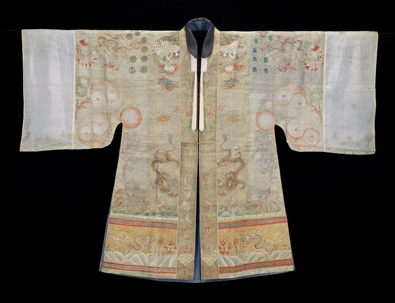 Lama priest robe of painted, pearl-grey gauze. All-over wave diaper in gold and blue. Conventional sacred pagoda motif in center back; small landscape medallions, clouds, bats,four clawed daagons, cranes, trigrams and various characters in shades of blue, red, pink, green, yellow and violet. Constellation discs of applied, gold foil. Bottom border of dragons, clouds, Eternal Sea, etc. Collar and front band with Buddhist symbols, clouds, white tiger. Cuffs painted with phoenix and dragon, and lengthened with bands of lime green brocaded silk. Lining of coarse blue cotton.