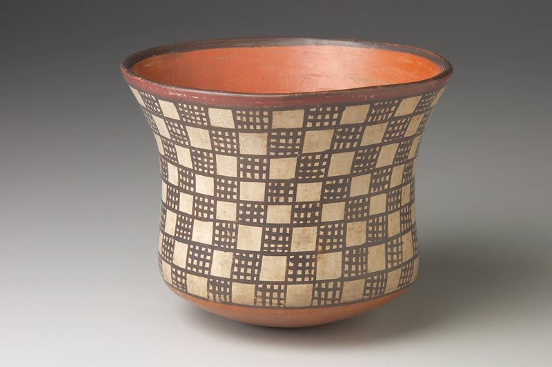 Large cup or bowl with slightly flared mouth and all-over design of checked and plain squares about 1/2 in. in area alternating in rows around sides. Such purely geometrical designs are rare in Nazca pottery.