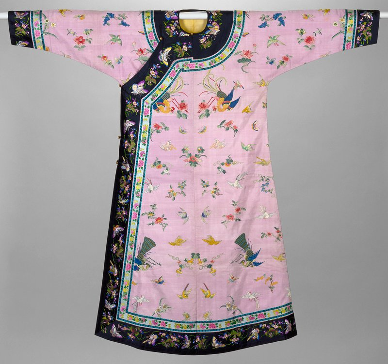 Robe of lavendar k'ossu with scattered design of phoenix, canaries, butterflies and flower blossoms in shades of green, peach, yellow, pink, rose, etc. Cuffs and border of black satin embroidered with a design of butterflies and flower sprays in satin, laid, and outline stitch; green, yellow, purple, blue, pink, etc. Inner border of pale blue satin embroidered with flower sprays and edged with trefoil band in band in black. Lining of lemon yellow silk.