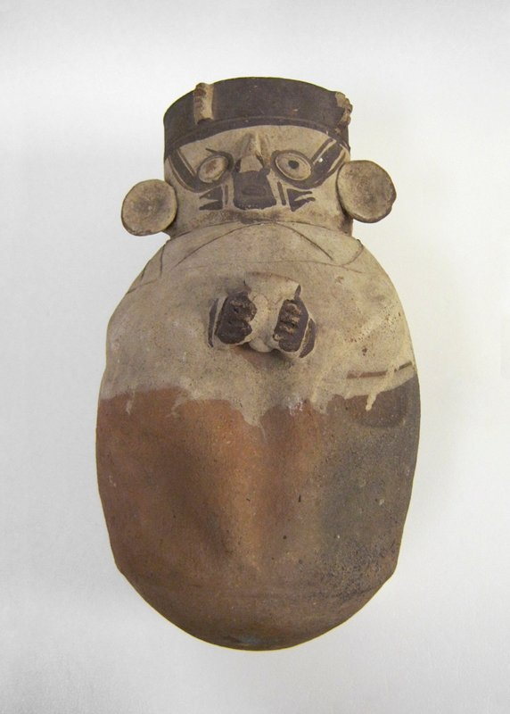 Large ceremonial vase representing a human figure holding a drinking cup against breast. The face is painted for ritual purposes, with features somewhat crudely modelled. With this vase was found the bowl, 43.2.20, in which it stood.