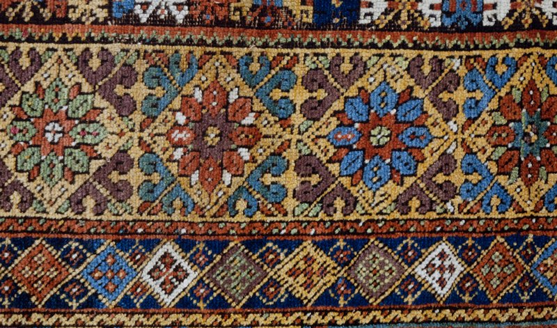 rug, prayer, with a red field fringed around the inner border with profile blossoms in dark blue. The prayer niche ahs a stepped outline in blue, white, gold, mauve, and red,a nd is flanked by red ewers in the green panel above the niche. A cross panel dircetly above carries a band of prayer-niche forms in blue, mauve, green, and gold on a red ground. Three borders, the wide central one filled with floral forms in diamond shaped panels on a gold ground, the inner on e of interlocking lozenges on a blue ground, and the outer on e of formalized blossoms alternatin, on the sides, with a gorizontal wine glass motif. Sides overcast in brown wool, ends finished with short warp threads. Ghiordes knot. Wool warp, wool woof, dyed red. Condition good.