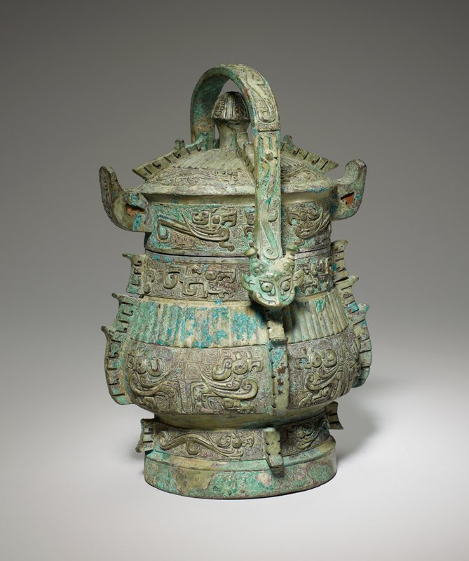 Wine can, so-called 'Yu', inscribed. A rich and varied decor is disposed in seven horizontal belts, of which five the foot belt, the two lower body belts, and the two on the domed lid, are divided into four panels by heavy, scored flanges with tooth-like projections. In the neck belt, flanges occur only on the long sides of the oval, where they form central ridges of the rudimentary t'ao-t'ieh. On the other sides the flanges are ousted by two handle attachments. The foot, the lower body, and the rim belts antithetical birds of three different types on a ground of squared spirals. The neck belt of the body and the lower belt on the dome of the lid have antithetical dragons of two kinds. Vertical ribs, typical of the B style appear on the middle belt of the body and the top belt of the lid. The knob is conical with incised cicadas all around. The bow handle, terminated by animals' heads with bottle horns, displays long gaping dragons. Patina grey-green patches of sharp green.