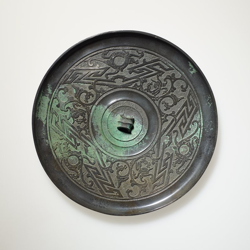 Mirror, round, with design of dragons and compound lozenges. Shou-chou type.