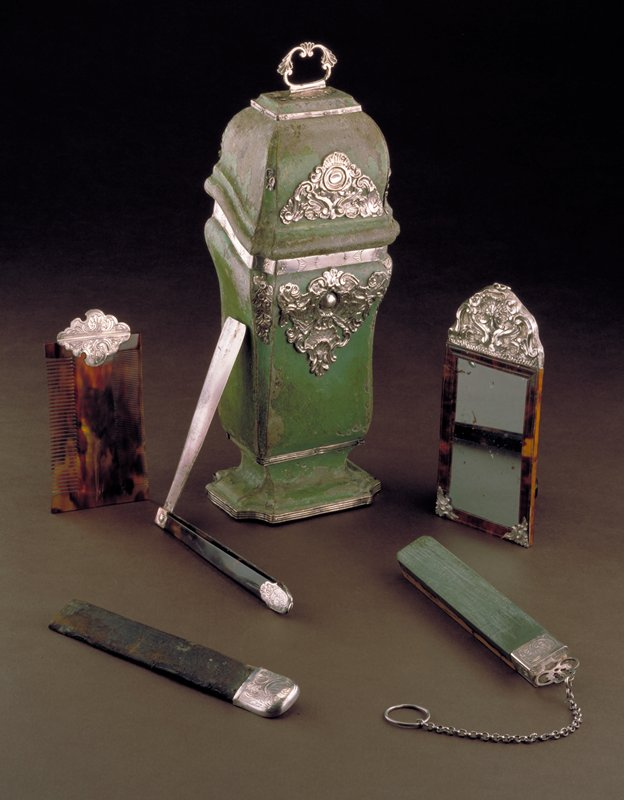 on base, wood painted light green, embellished with rococo silver ornaments including silver handles, lined in crimson silk, containing mirror, strap, comb, 6 razors and strap