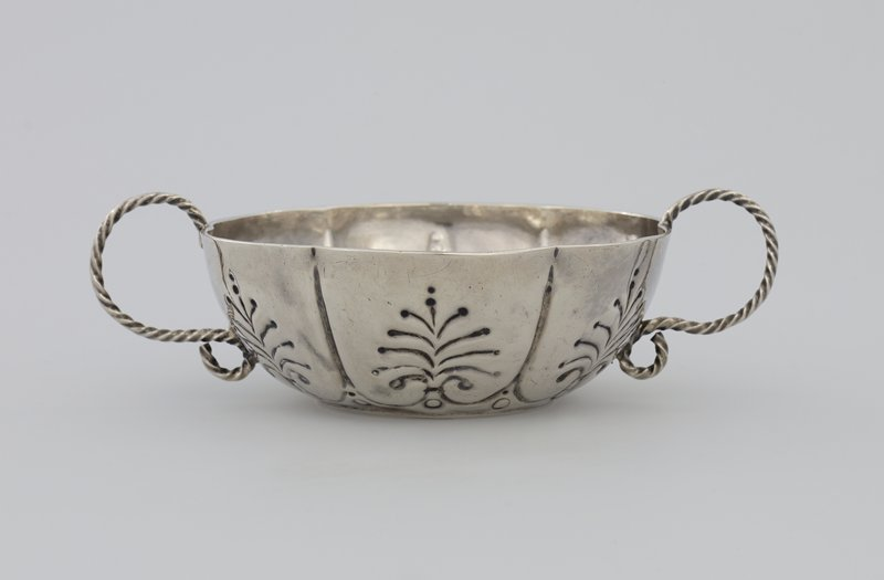 two-handled silver bowl; drinking; shallow, with six vertical flutes forming shallow lobes with chased palm-leaf decoration; flat bottomed; two twisted wire 'S' scroll handles