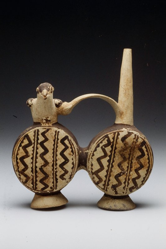One of a pair of Whistling Huaco, each consisting of two round pots joined by a convex handle, one side decorated with a dove and the other containing a spout; pottery