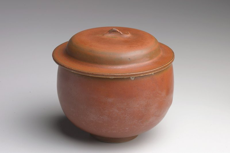 small round-bottomed bowl with short foot; sides slightly flaring inward; slightly domed lid with wide lip; small finial; brown glaze