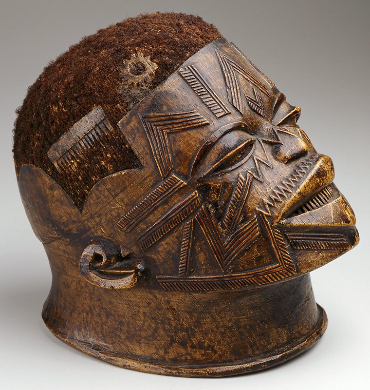 Helmet Mask, wood and hair, full head tilted slightly upwards, fully scarified face and geometrically shaven head.