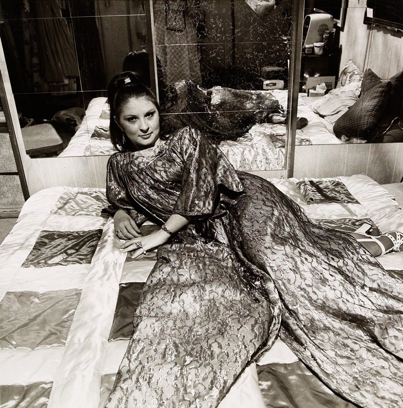 woman lying on bed with long flowing robe spread around her. mirrored wall behind her