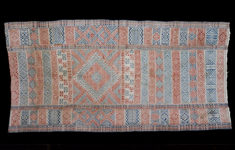 Chaksay Pankhep, royal/religious lap cover; silk/cotton brocade on cotton background; red and blue discontinuous supplementary warp and discontinuous supplementary weft pattern on neutral ground; in 3 sections; one end hemmed, one unfinished.