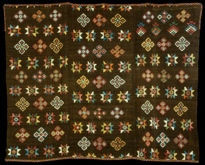 Yattha Charkhab; triple panel wool brocade on wool background; brown ground with multicolored discontinuous supplementary weft design; bound along non-selvedge edges with plaid cloth.