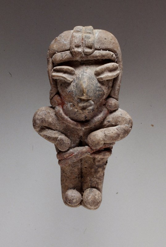 Standing female figure, solid buff clay with traces of red pigment, applique headband, crossed waistband, hands held to chest.