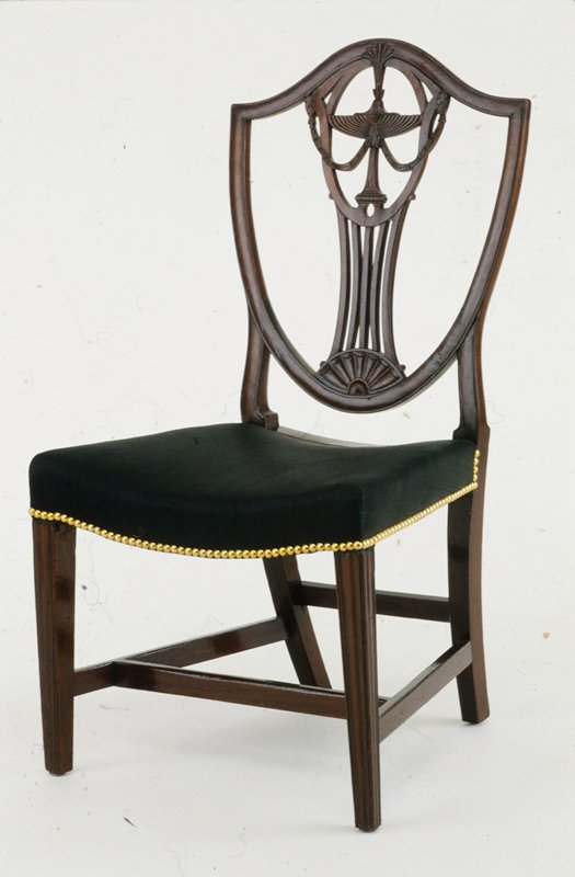 Hepplewhite Side Chair, c.1800 from Rhode Island. Mahogany with maple and pine as secondary woods. Rhode Island type of shield-back chair with carved urn, molded legs and saddle seat. Pair with 85.17