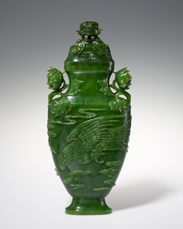 vase, emerald green jade with cover and small ivory base 2 x 4-1/2 in. H. 11-1/2 inches, W. 5-1/2 inches. Vase, emerald green spinach jade, with cover. On each side of the body a phoenix in flight surrounded by cloud forms and trailing streams in relief. Handles and finial of bold peony buds deeply undercut.