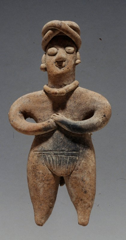 STANDING FEMALE FIGURE, hands held to chest, applique facial details, headband, necklace with double pendant, loincloth with rear tassel, unburnished buff clay, West Mexican, Colima