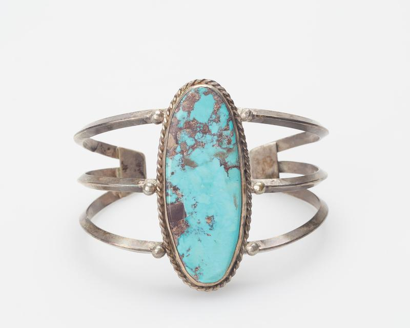 3 carinated silver wires; set with large central elliptical Bisbee turquoise surrounded by twisted wire and teardrop decoration J.#326, Cat.#59