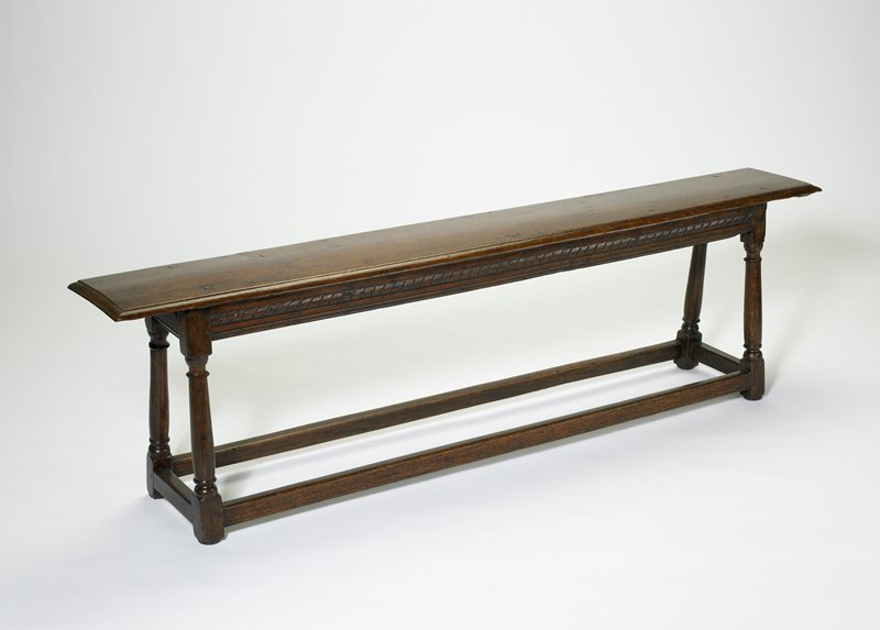 Bench; narrow, of long form type with raked legs. Carved apron
