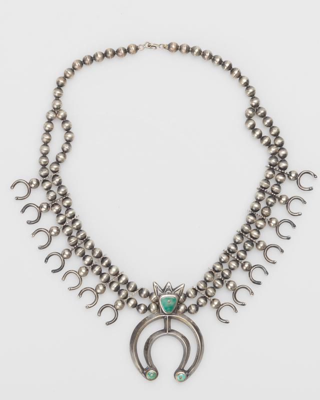 Double strand of silver beads becomes single strand; on each side of main naja 7 small najas attached to bead with notched, double pierced extension; cast, carinated large naja has 3 turquoise (one triangular and two round) drilled and filled with silver spikes, crown at top; string with metal clasp. J.#415, Cat.#473.