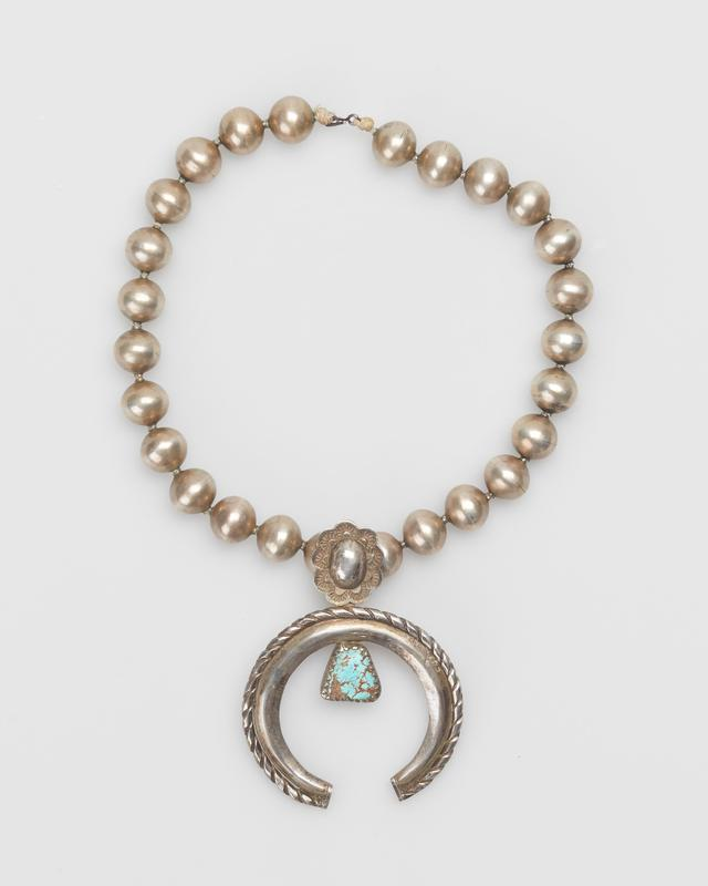Single strand of large silver beads; naja of half-round hammered wire enclosed by twisted flat wire, trapezoidal Cerrillos turquoise in serrated bezel at center, scalloped edged ornament, with repousse and stamped decoration above shank, tied into main strand, metal clasp. J.#404, Cat.#406.