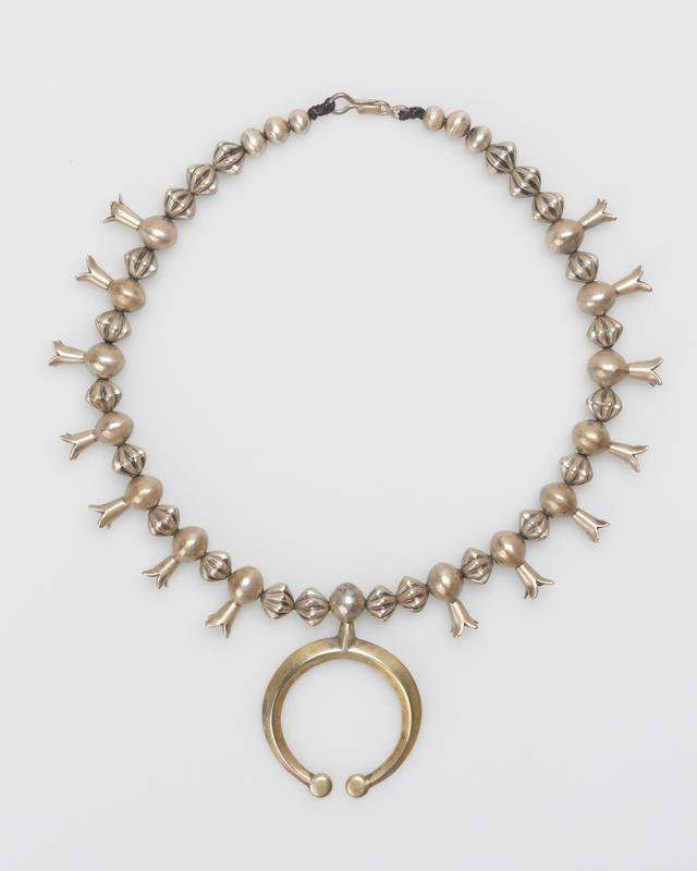 Single strand of gadrooned beads; fourteen squash blossom beads strung directly on necklace; cast carinated naja with bead as shank. J.#504, Cat.#482.