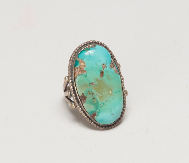Oval turquoise on a 3-branched split shank silver ring; set with large oval turquoise, silver bead wire with teardrop decoration. J. #944, Cat# 832, Illus p. 177