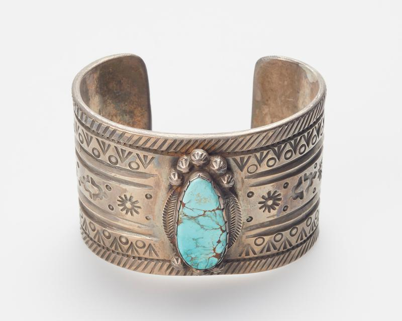 Bracelet with stamped design, single oval turquoise with notched bezel and silver beads at top and bottom. Joe Chee.