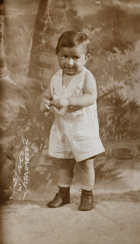 small boy standing, grasping finger