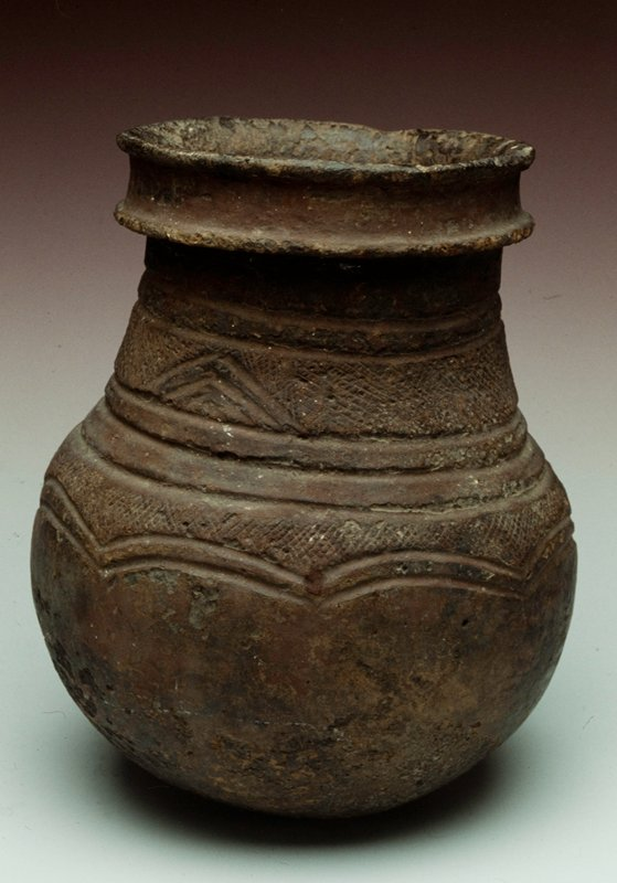 Wide mouthed globular pot with band around neck of incised line design. Downward pointed scalloped design.