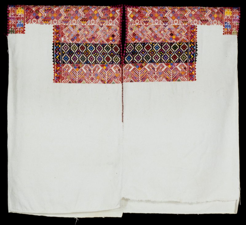 Two panel huipil with slit neck opening and randa extending 1/2 way down front; white ground cloth with patterning primarily in red with pink, green, black, blue, orange and yellow; design consists of stylized bird and tree patterns, diamonds and other geometric motifs.