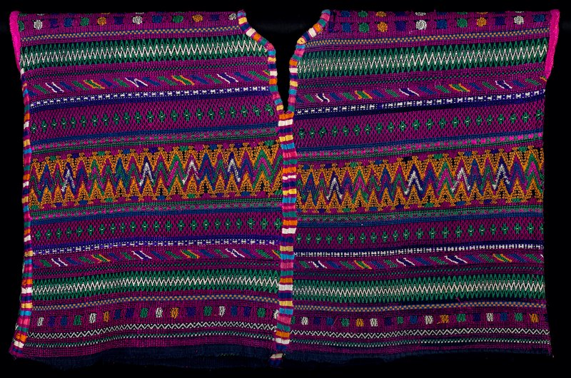 Two three-selvage panels; discontinuous supplementary weft patterning with embroidered randas on center and side seams, additional embroidery at neck and arm openings. Indigo ground with geometric designs of zigzags, lozenges, arranged in bands across the garment predominantly in magenta, green, white, blue and yellow.