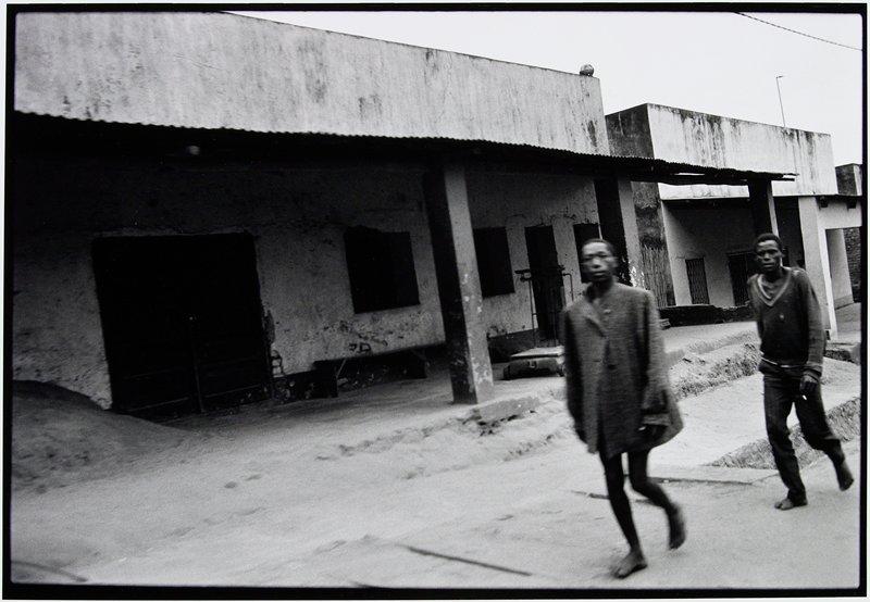 two men walking down an empty street toward camera
