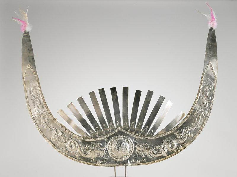 thin sheet of metal cut into horn shape with a fan of twelve points rising above center, central design, pounded metal of two phoenixes and dragons facing a central emblem, or inscription, and feathers attached to points of horns