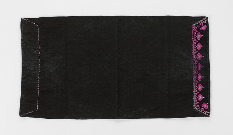 black rectangular cloth with fuchsia embroidery at each edge on opposite sides of cloth