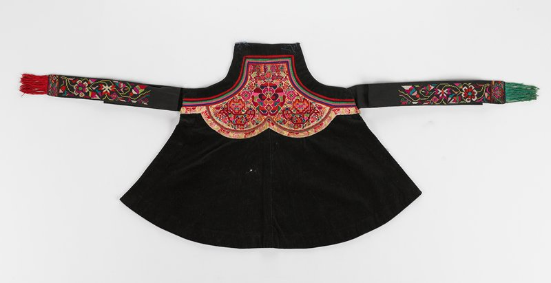 black apron with red and other colored embroidery UC to stripes of trim color near top of apron red, purple, pink, blue, red; multicolored embroidery and tassels at end of ties