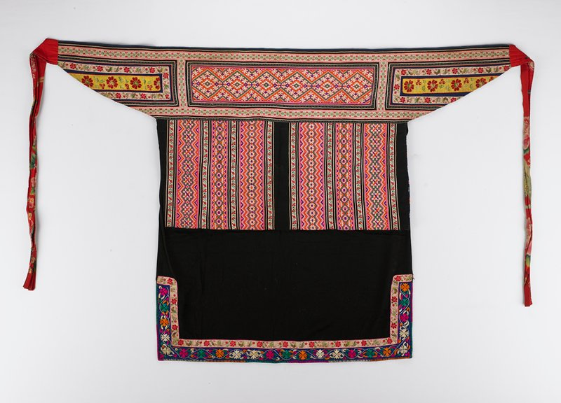large black apron with loose flap beneath waistband; two embroidered bands at hem and lower corners; three horizontal embroidered bands on waistband; framed by smaller bands; flap has six vertical embroidered bands framed by smaller bands; back ties are made of red cloth with printed floral design