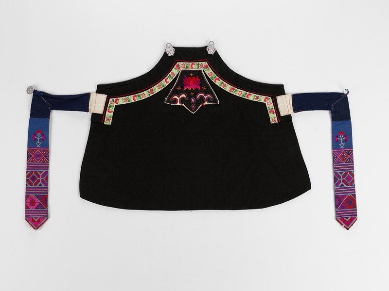 black body apron with green band and two metal loops at top, ties are made of two parts sewn at an angle to one another; intended to be buttoned and have both ends hang in back; ends of ties embroidered