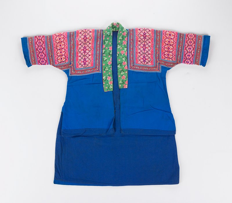 bright blue open front coat; green trim with printed flowers around neck; upper body and sleeves covered on both sides with bands of embroidery