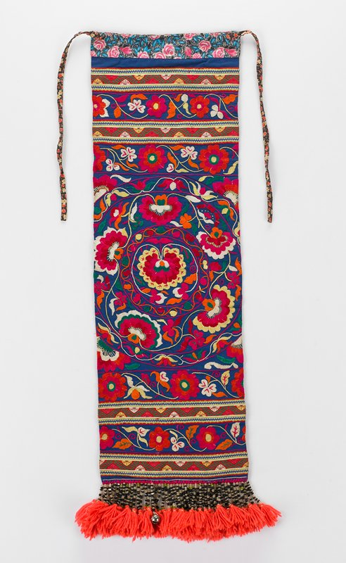 printed back fabric of black, brown, yellow and red; bottom edge lined with strands of beads and pink tassels and two bells; overall blue field with large central circle and triple banding above and below of floral design