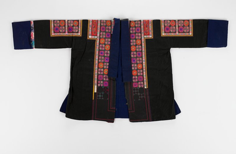 black coat with blue cuffs; multicolored embroidery with octagonal design on arms and bordering front opening; two bands of embroidery with the same design run the length of the back of the coat