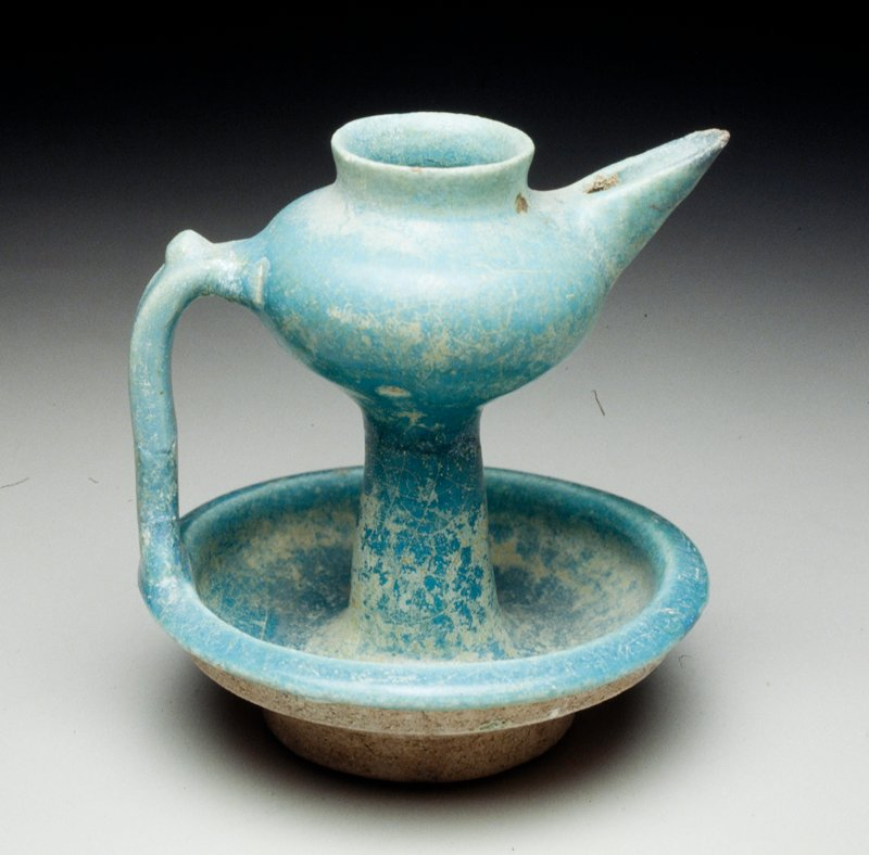 saucer base; strap handle; formed spout; blue glaze
