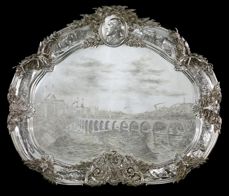 'Hill tray' presented to James J. Hill by seventeen prominent Minneapolis businessmen, kidney shaped in outline, has large flat central are engraved with a view of Minneapolis showing the Stone Arch Railroad Bridge completed 22 Nov. 1883; around the perimeter of the scene, within molded reserves, are eight vignettes representing significant incidents in J.J. Hill's career, separated by a profile medallion of Hill (top center), six animal head trophies, and a monogram of Hill's initials; all parts individually designed and manufactured, separately cast and joined to central panel
