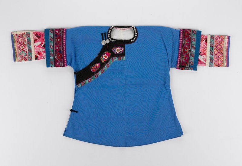 blue body with three banded cuffs and sewn in sleeves; side and neck button with two bands of floral design from neck to right side