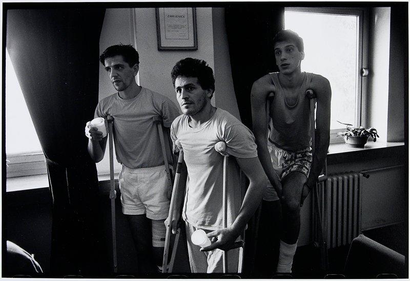 three men on crutches near window