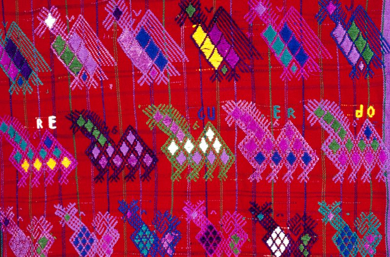 red field of plaid; DSWP of multiple colors; diamond bands at short sides, bands of bird and flower patterns; three stripes of green, purple and blue at sides and center