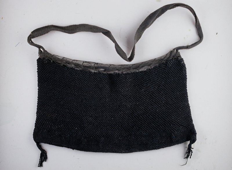 handled black bag; tassels at both bottom corners; open work around upper rim opening