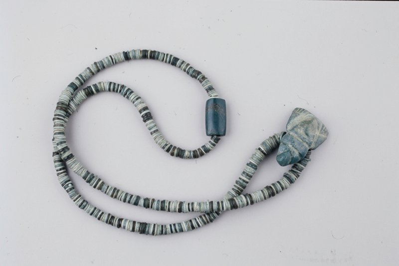 dark and light green jade striped necklace; pendant and large tubular jade bead opposite each other