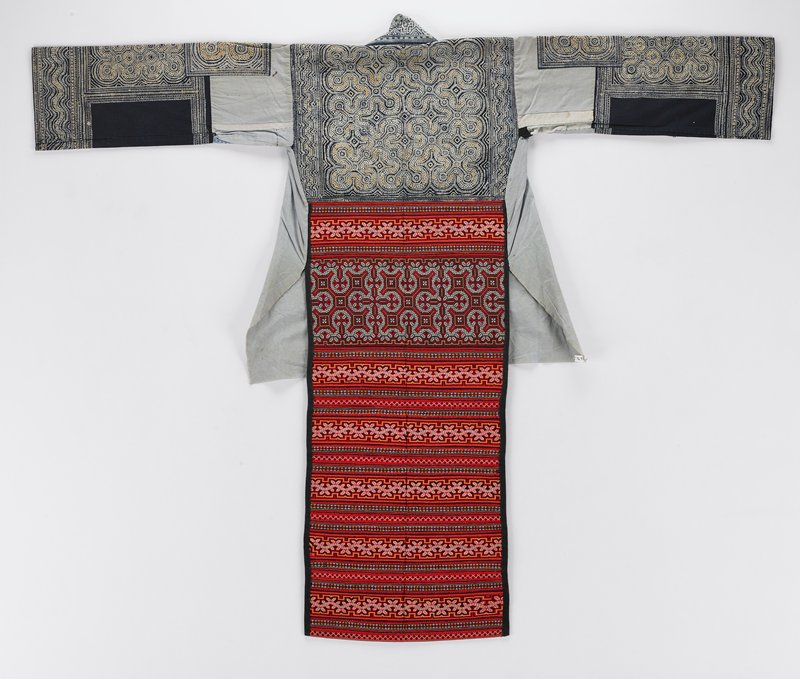 tan field, black cuffs and blue border around bottom front; applique diamonds on front and back in a variety of colors with floral and script designs, two central mirrors on front and one central on back