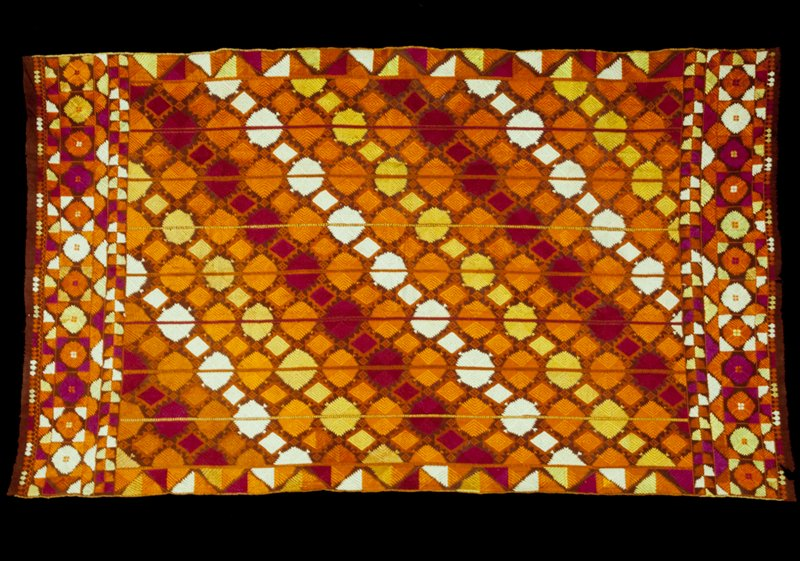 embroidery, brown field, geometric square and triangular patterns of fuchsia, yellow, orange and white